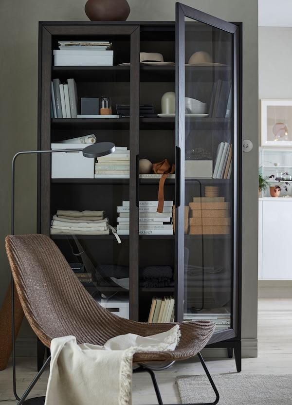 Crno-smeđa IKEA REGISSÖR vitrina ispunjena kutijama, knjigama i čašama iza stolice.