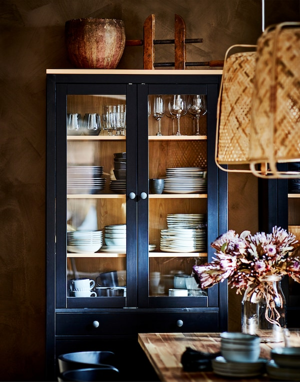 Crnobraon HEMNES vitrina s vinskim čašama i posuđem, iza trpezarijskog stola s cvetnom vazom.