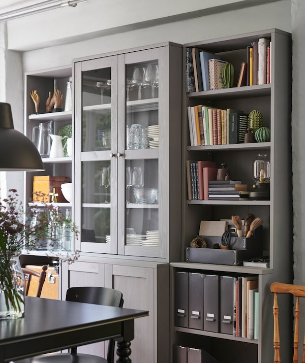 Crockery, books and files in a storage unit with open shelves and glass-fronted cupboards next to a dining table.