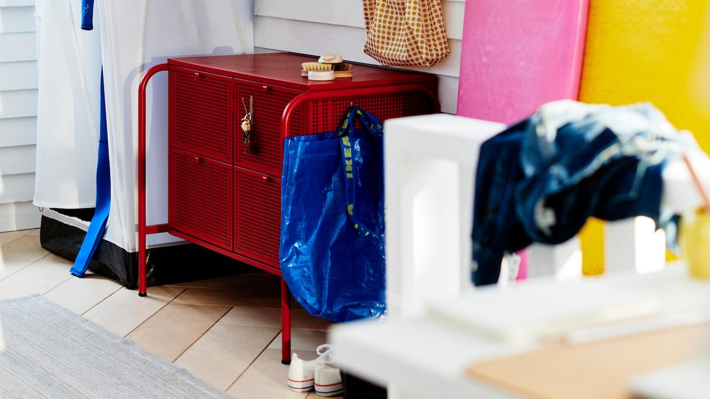 Crvena NIKKEBY komoda s ladicama okružena je različitim dodacima za predsoblje u sobi sa zidovima prekrivenim bijelim daskama.