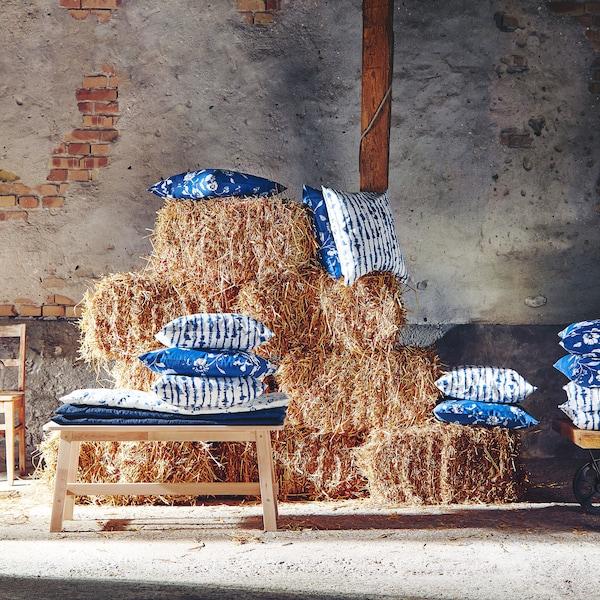 Čtvercové, modro-bílé povlaky na polštáře BLÅGRAN a SIMSPORRE na hromadě sena.