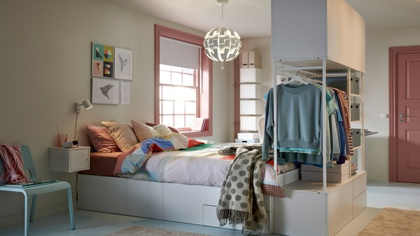 Cuarto de estudante en tons pastel cunha cama no centro con almacenaxe integrada na parte inferior e almacenaxe con roupa pendurada nos pés.
