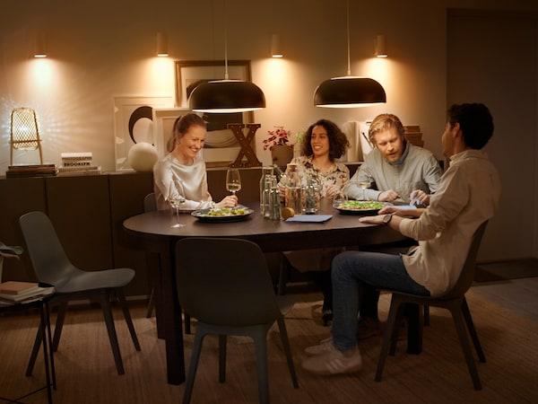 Cuatro amigos comiendo en una mesa extensible BJURSTA debajo de lámparas de techo controladas por un sistema para obtener luz inteligente y mucho más en casa.