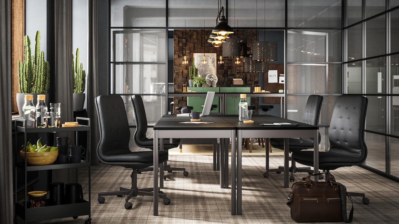 Cuatro mesas IDÅSEN negro/gris oscuro con sillas de color gris oscuro expuestas en una sala de conferencias con paredes de vidrio.