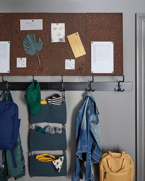 Cuatro tableros de notas SVENSÅS en marrón oscuro, montados en la pared, con postales, horarios y notas colgados.
