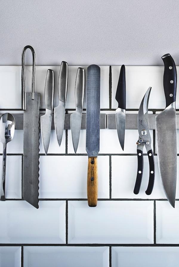 Cuchillos y utensilios de cocina almacenados en una barra magnética que está montada en la pared de azulejos blancos de una cocina.