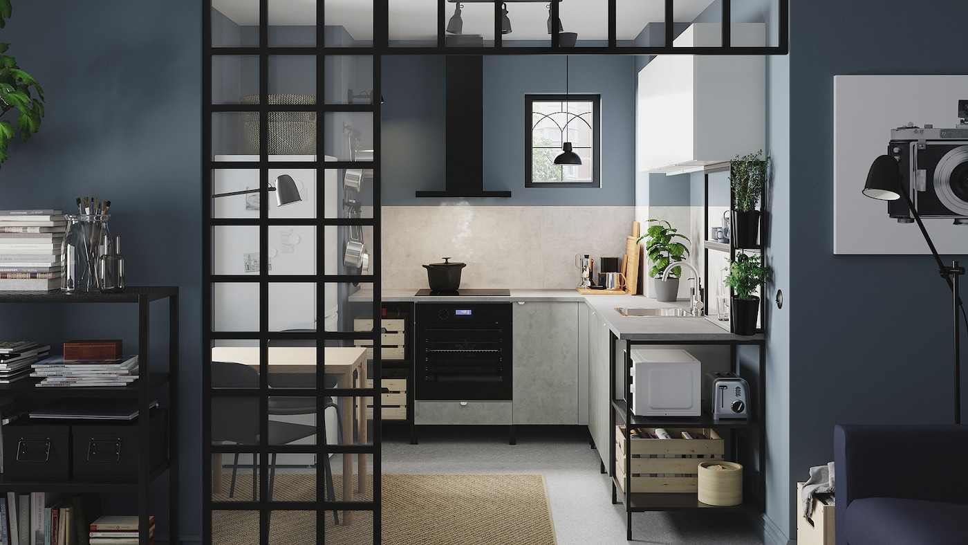 Cucina angolare in antracite/effetto cemento/bianco con mobili a giorno e con ante, lampade nere, erbe aromatiche in vaso e tappeto in iuta.