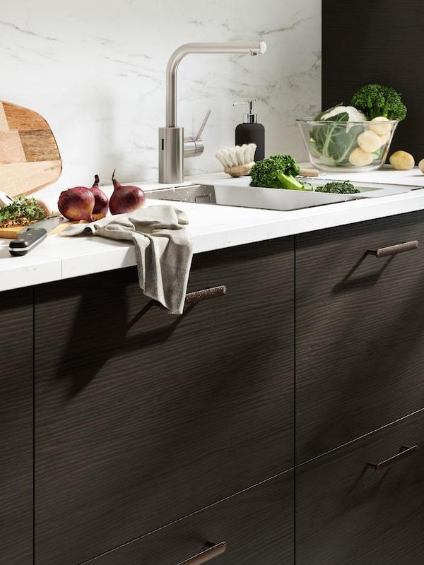 Cucina con cassetti ASKERSUND marrone scuro e piano di lavoro KASKER effetto marmo su cui sono appoggiati cipolle rosse, broccoli e un cavolfiore.
