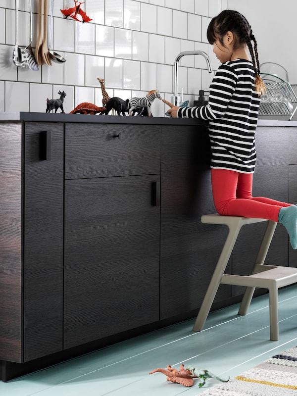 Cucina con pareti piastrellate di bianco e cassetti ASKERSUND marrone scuro. Una bambina gioca sul piano di lavoro.