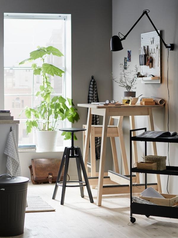 Cucina con tavolo bar NORRÅKER usato come postazione di lavoro, con sgabello bar DALFRED e un carrello con accessori.