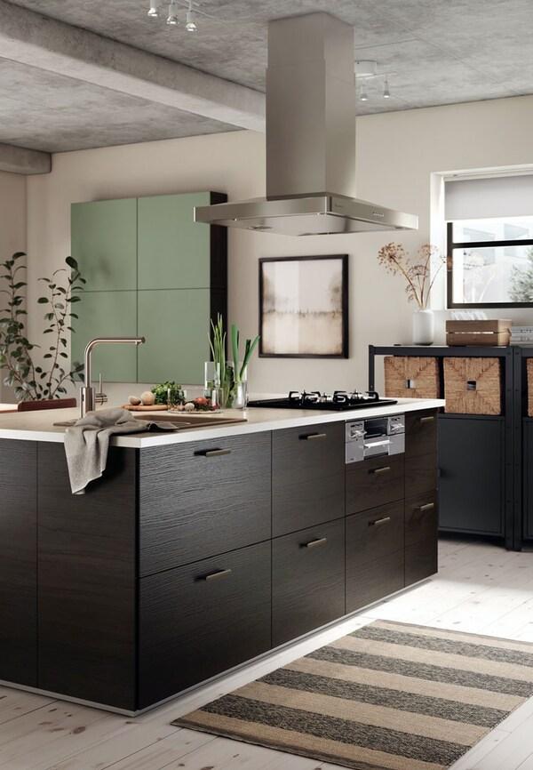 Cucina IKEA marrone nero con fornello al centro e cappa in acciaio appesa al soffitto. - IKEA