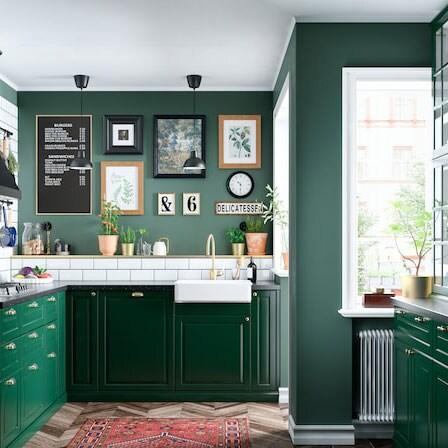 Cucina verde scuro con piastrelle bianche, ante a vetro, miscelatore color ottone e una parete con tante cornici – IKEA