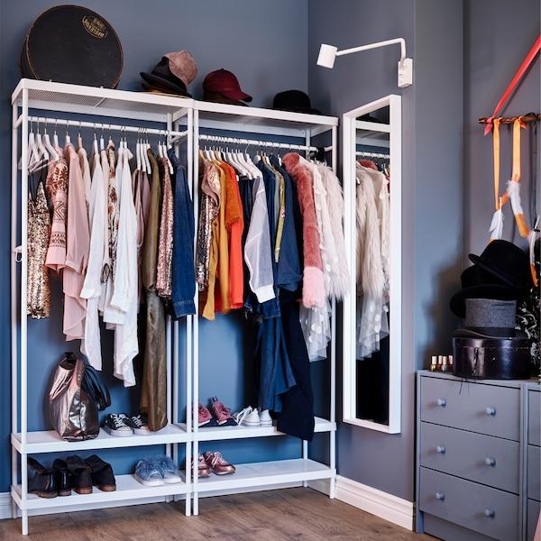 Cuier alb cu spațiu de depozitare pantofi, o oglindă albă, o aplică albă și o comodă cu sertare gri-albastru.