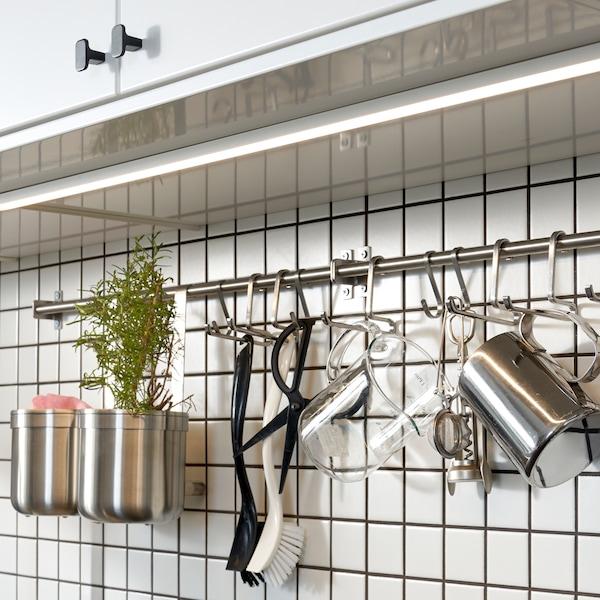 Cuisine aux éléments équipés de portes blanches. Sous ces derniers on voit un mur carrelé de blanc sur lequel est fixé un rail garni de crochets en acier inoxydable.