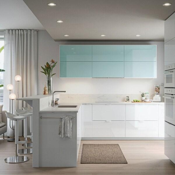 Cuisine aux lignes sobres, portes brillantes en blanc et turquoise, planche à découper et blender avec fruits.