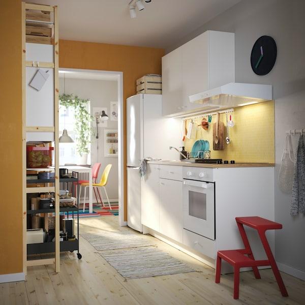 Cuisine aux tiroirs et portes en finition brun-rouge foncé brillant et armoires ouvertes TUTEMO en finition anthracite accueillant des bocaux alimentaires en verre.