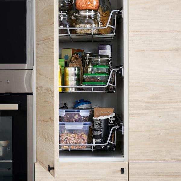 Cuisine avec armoire haute dont la porte en finition frêne clair est ouverte, dévoilant des corbeilles fil, des récipients pour aliments, etc.
