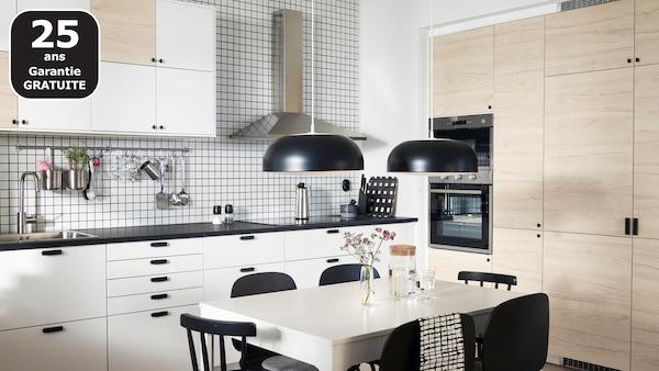 Cuisine avec portes en finition blanc et frêne clair, deux suspensions noires, une table blanche et des chaises noires.