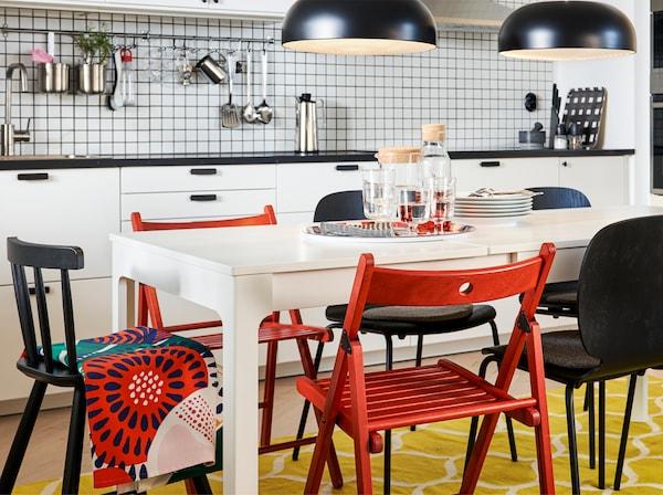 Cuisine avec table à rallonge blanche en extension maximale, chaises rouges et noires, tapis jaune/blanc et deux suspensions noires.