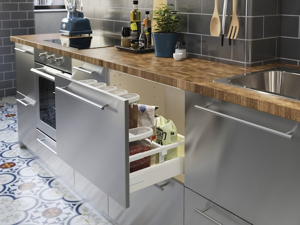Cuisine en acier inoxydable avec plan de travail en chêne/plaqué. Un tiroir ouvert avec divers produits secs à l'intérieur.