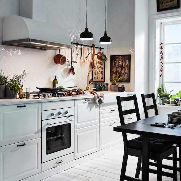 Cuisine en finition blanc cassé BODBYN éclairée par deux suspensions noires. Sur la droite, une table et deux chaises en finition noire.
