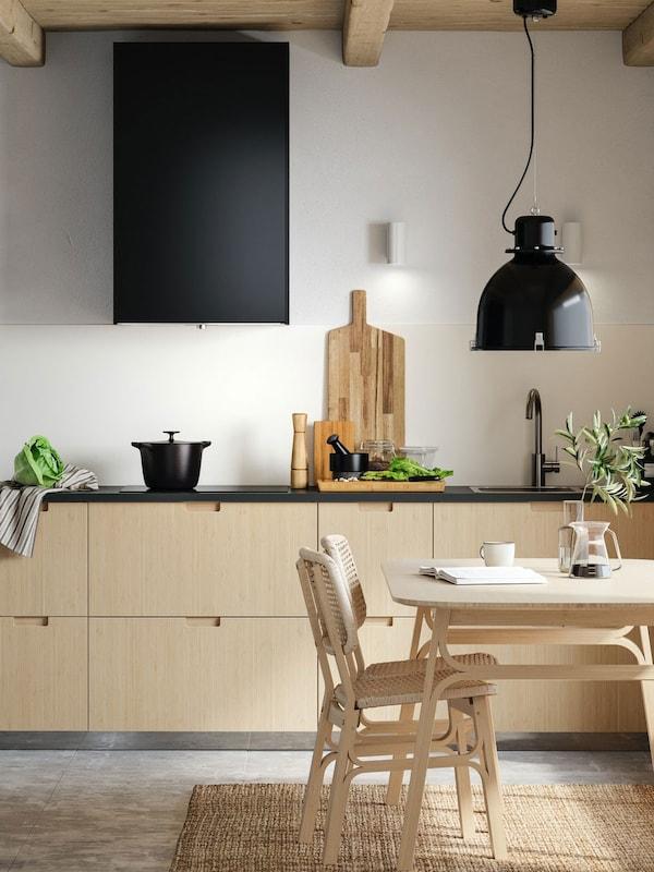 Cuisine minimaliste avec faces de tiroirs en bambou clair, portes noires, table et deux chaises en bambou clair.
