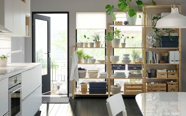Cuisine monochrome avec des plantes, de la vaisselle et des papiers sur des étagères en bois.