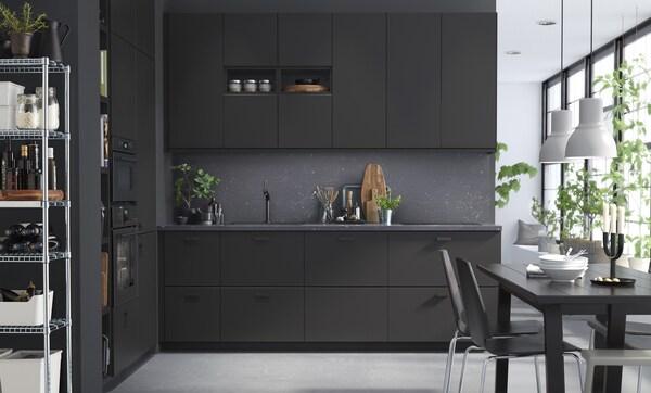 Cuisine noire avec grandes fenêtres et table de salle à manger noire.