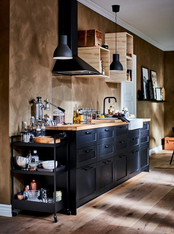 Cuisinette richement équipée avec petites armoires murales ouvertes, hotte aspirante et façades de tiroirs LERHYTTAN de couleurfoncée.