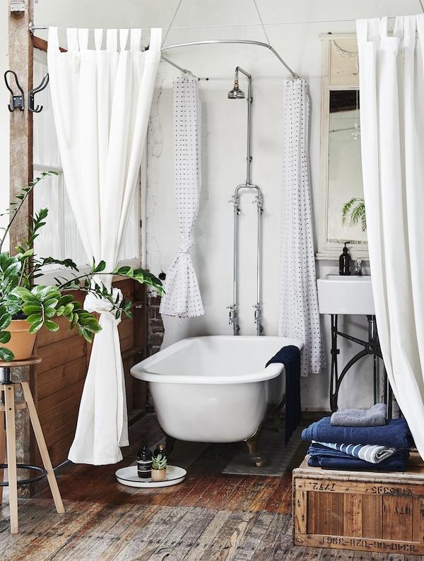 Curtains and plants around a bath tub.
