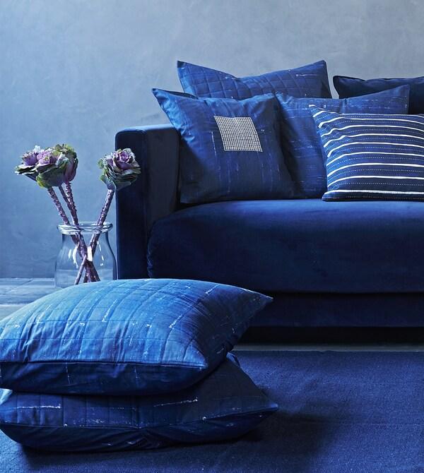 Cuscini con fodere decorate con motivi nelle tonalità del blu su un divano blu - IKEA