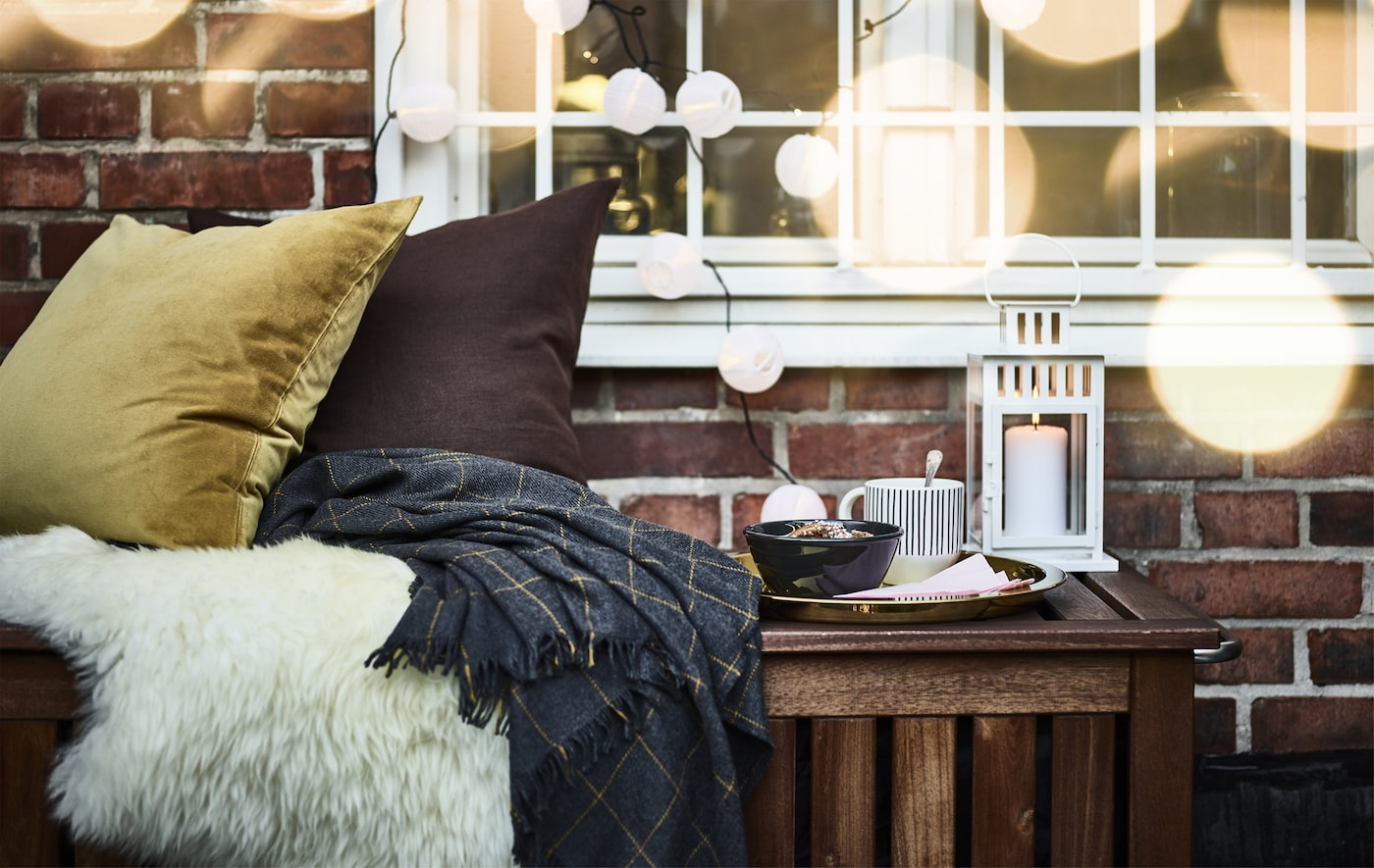 Cushions and throws, a tray with a bowl and a cup, and a lantern on a bench outside a window hung with a lighting chain.