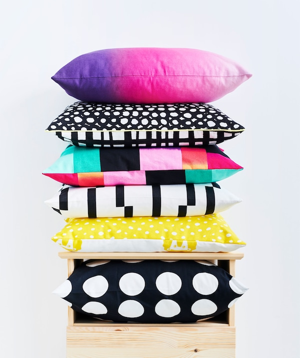 Cushions – black and white, graphic patterns, sharp coloring in a mix – piled in a stack on top of a chest of drawers.