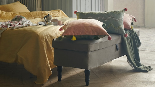 Cushions in KLARAFINA and MOAKAJSA covers lie on a STOCKSUND bench at the foot of a bed with yellow PUDERVIVA bed linen.