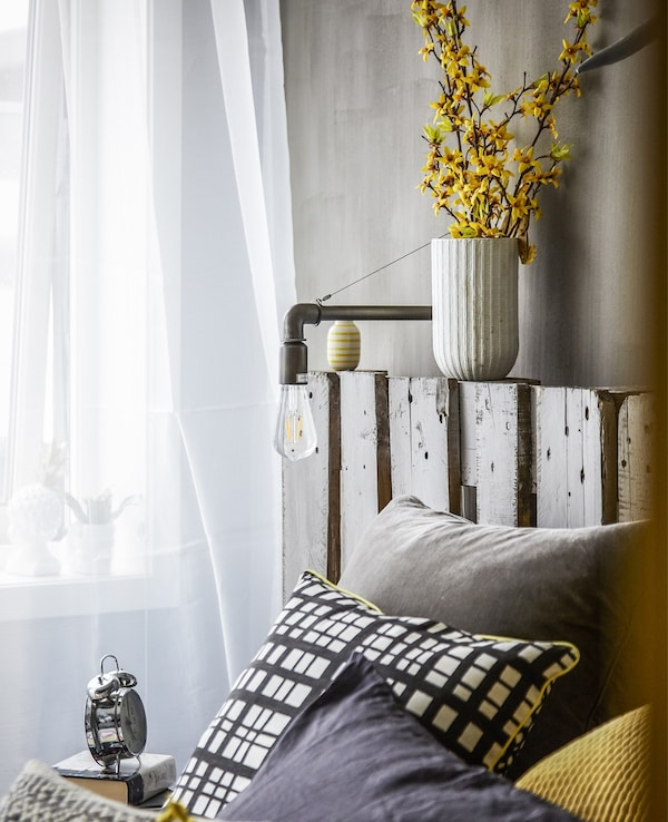 Cushions layered on a bed and voile curtains.