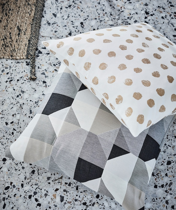 Cushions with simplistic, strong dot and block patterns laying on terrazzo floor tiles.