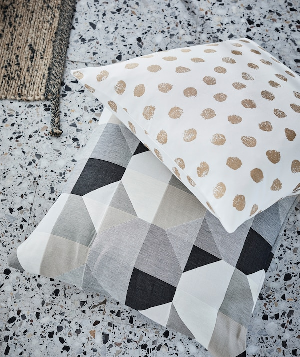 Cushions with simplistic, strong dot or block patterns create a splash wherever they land – even on terrazzo floor tiles.