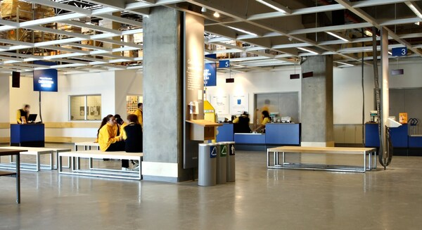 Customers waiting at the IKEA returns department with tables and benches surrounding them.