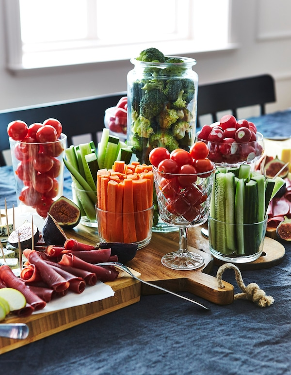 Cut fruits and vegetables arranged in glass containers, on chopping boards, on a table.