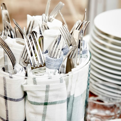 Cutlery wrapped in blue and white tea towels