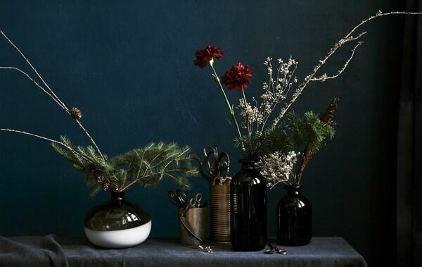 Cvjetni aranžmani u vazama različitih veličina uz crnu pozadinu od tkanine.