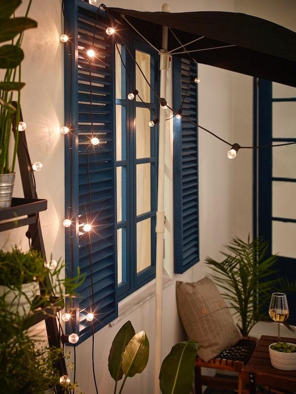 Czarna girlanda LED IKEA UTSUND zaaranżowana na ścianie balkonu w nocy.