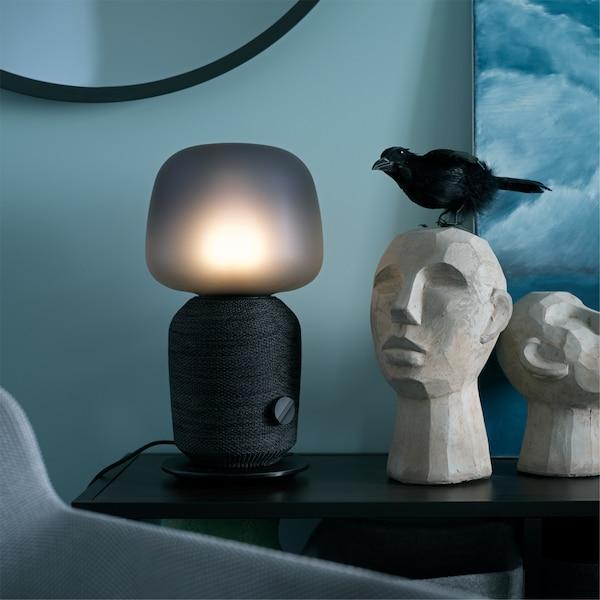 Czarna lampa stołowa SYMFONISK stojąca na czarnym stole obok dekoracyjnych elementów w niebieskiej sypialni.