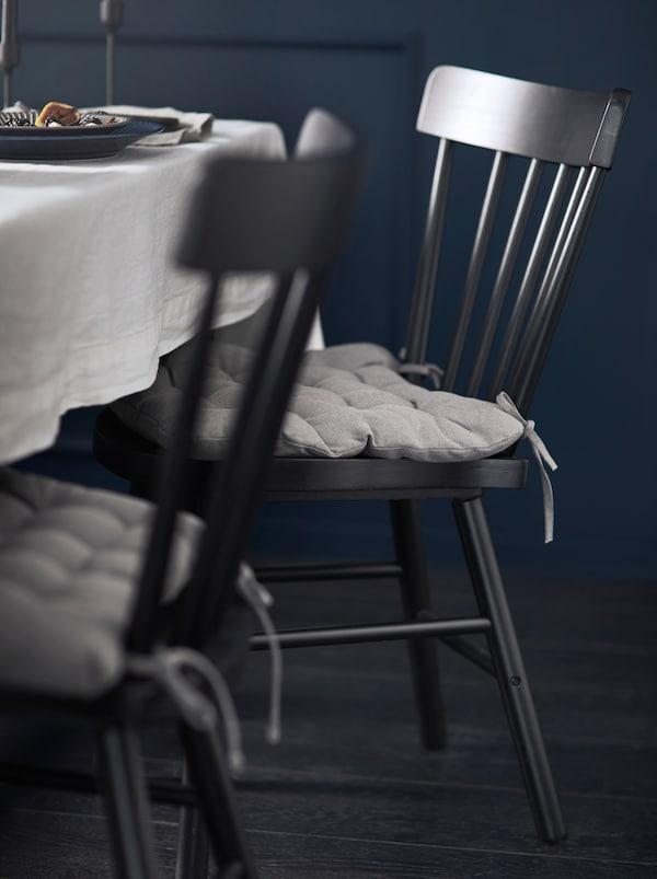 Czarne krzesła NORRARYD z szarymi poduszkami na siedzisku ustawione przy stole z jasnym obrusem w pokoju z ciemnymi ścianami.