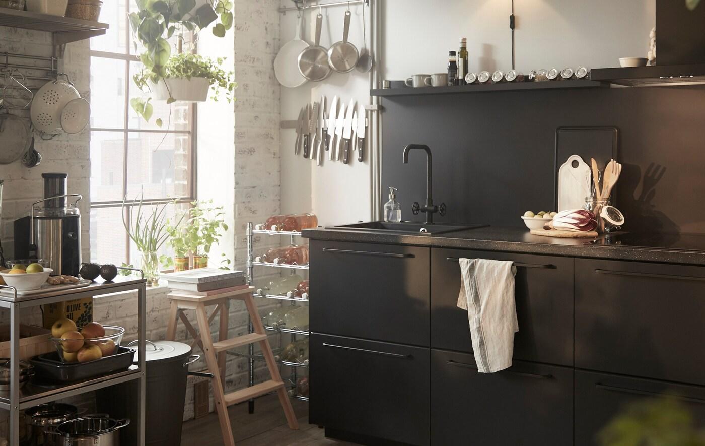 Czarne szafki kuchenne ze zlewem, metalowy wózek i przybory przechowywane na szynach przy oknie.