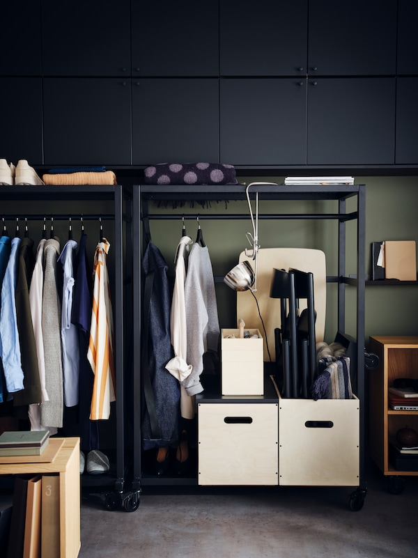 Czarne szafki na kółkach RÅVAROR wypełnione ubraniami i pudełkami RÅVAROR. Na górnej półce leży złożony pled RÅVAROR.