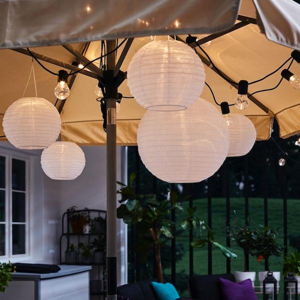 Czarny łańcuch świetny i okrągłe lampy wiszące zawieszone pod otwartym parasolem, dające ciepłe i przytulne światło.