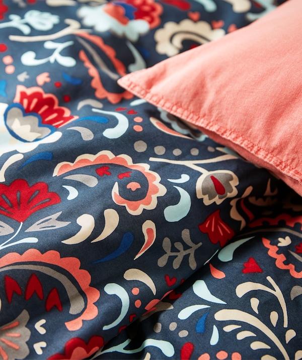 Cześć łóżka z pościelą w jaskrawych kolorach, ozdobioną tradycyjnym szwedzkim wzorem kurbits.