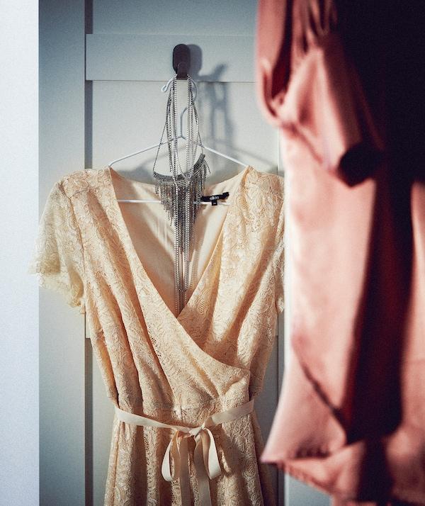 Część otwartych drzwi do szafy z haczykiem, na którym zawieszono naszyjnik i elegancką sukienkę bez rękawów na wieszaku.