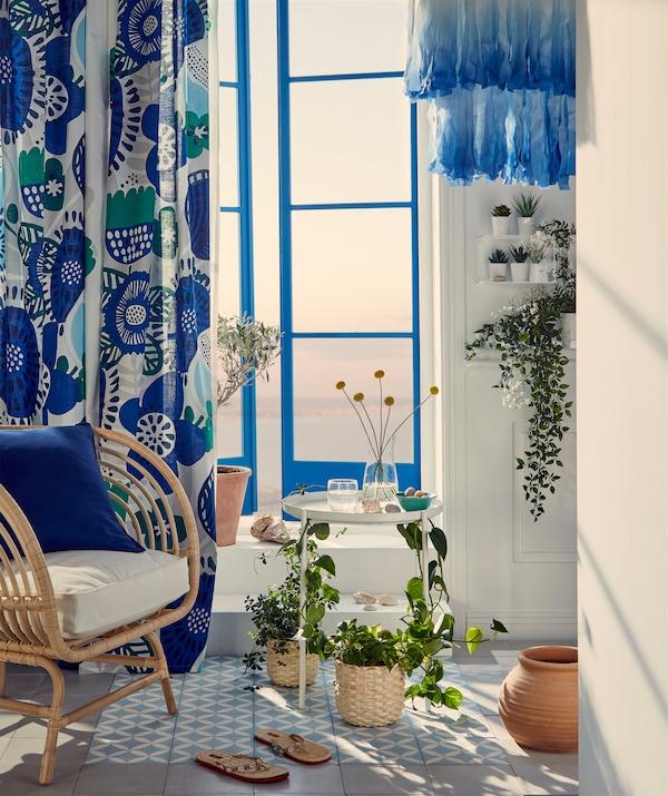 Część pokoju obok okien w stylu francuskiego balkonu. Wiklinowy fotel i owinięty roślinami, wąski stolik z tacą i półki ścienne.